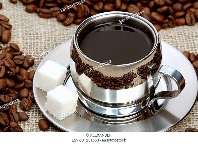 Cup of coffee with lump sugar and beans