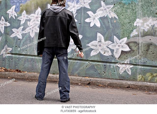 Man with Spray Paint in front of Graffiti
