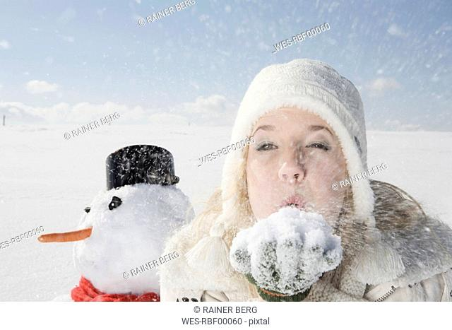 Germany, Bavaria, Munich, Young woman blowing snow off hand, portrait