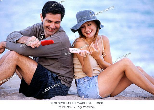 couple eating popsicales at the beach