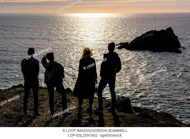 Four friends enjoy a spectacular summer evening on East Pentire headland in Newquay in Cornwall
