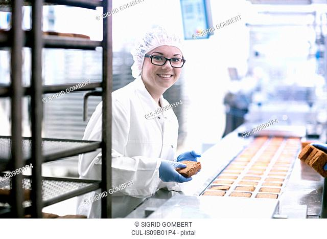 Factory worker on food production line looking at camera smiling