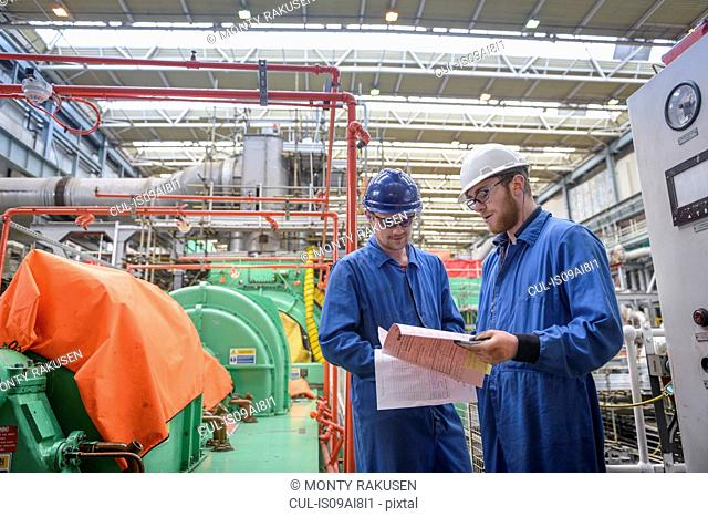 Engineers discussing paperwork during power station outage