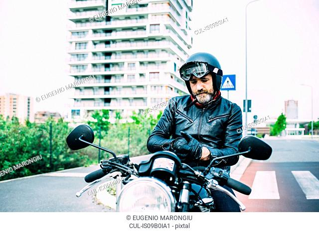 Mature male motorcyclist sitting on motorcycle putting on gloves