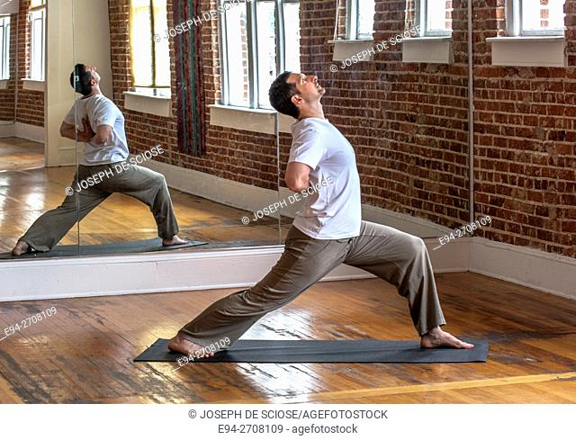 A 38 year old man and yoga expert doing yoga poses, indoors