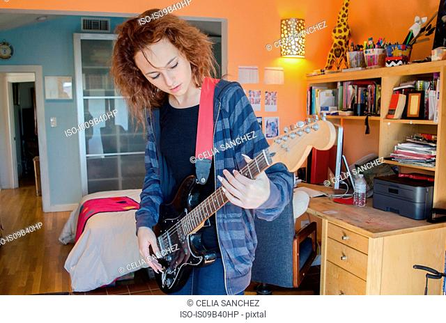 Teenager playing electric guitar in bedroom