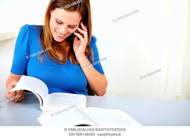 Portrait of a lovely pretty woman browsing a book while is speaking on cellphone at home indoor