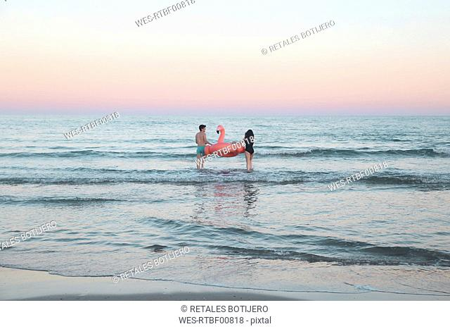 Back view of young couple walking into the sea with inflatable pink flamingo