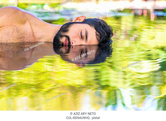 Bearded young man lying on side in water, illusion of mirror image, Taiba, Ceara, Brazil