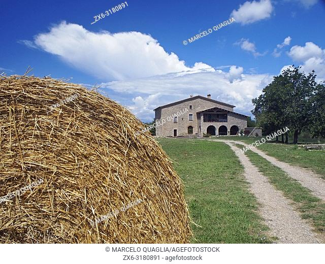 Hay bale and typical farmhouse of Catalonia (Masia) at Olost village countryside. Lluçanès region. Barcelona province, Catalonia, Spain