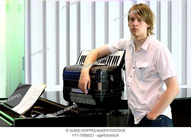 Young, male student at conservatoire playing the accordion at graduate level
