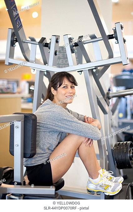 Woman sitting on exercise machine in gym