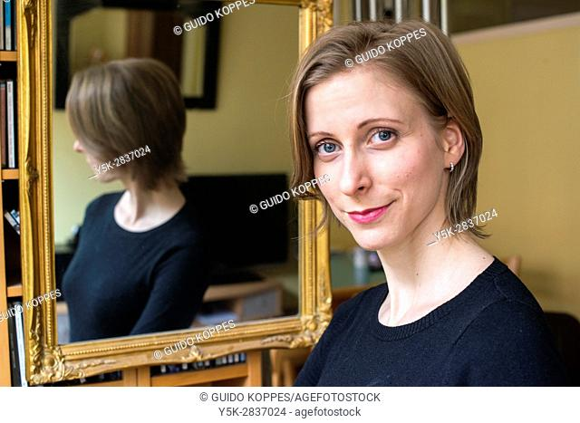 Tilburg, Netherlands. Young adult caucasian woman showing the results of a make up session, using a living room mirror