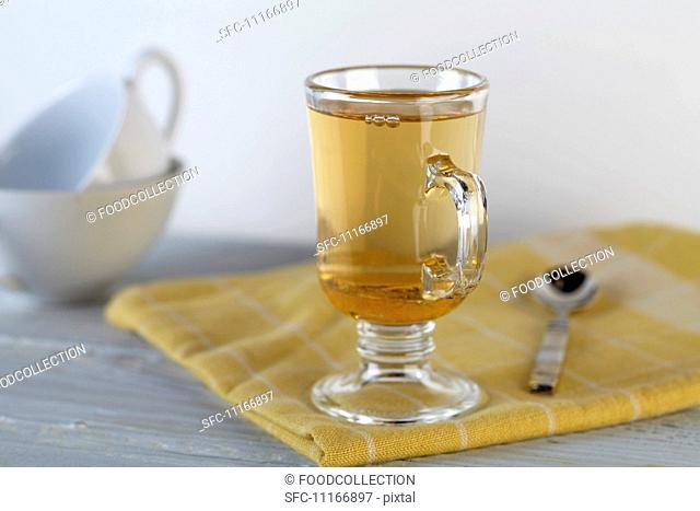 A Glass of Honey Ginger Apple Cider on a Yellow Towel