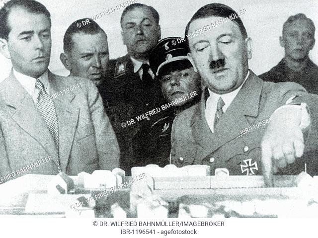 Adolf Hitler discusses a model of a building with Prof. Albert Speer, historical photo circa 1936