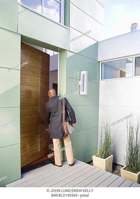 African American businessman entering home