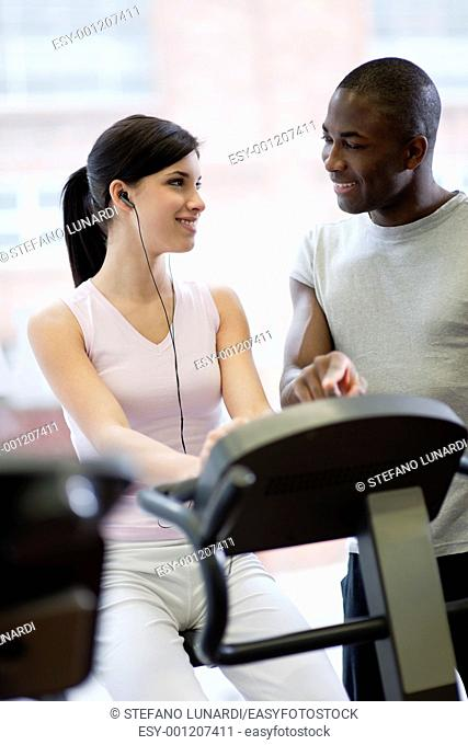 Personale trainer shows exercises to a young woman