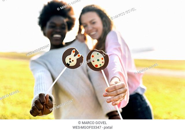 Two happy friends holding Easter chocolates