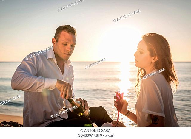Young couple drinking champagne on beach, Castiadas, Sardinia, Italy
