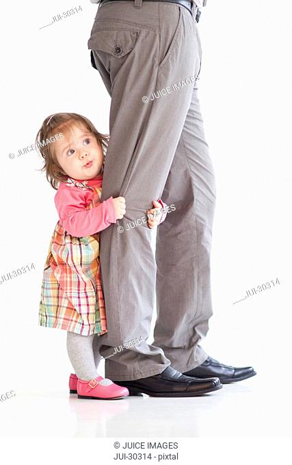 Baby girl clinging to father's leg