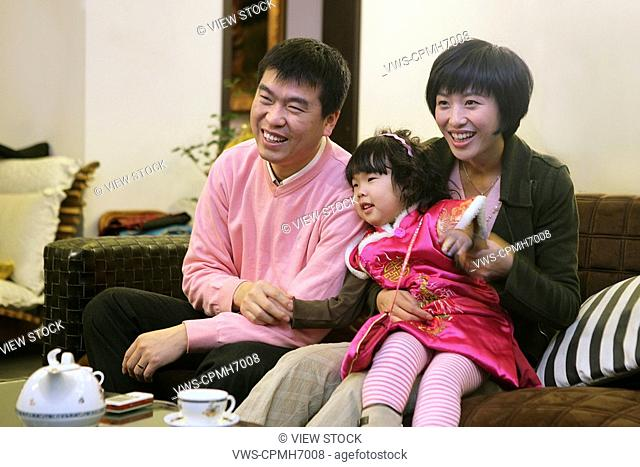 Chinese young couple with their daughter watching TV