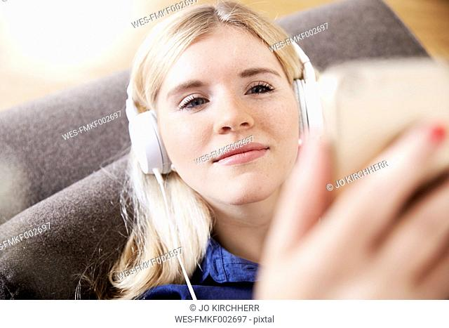 Portrait of young woman listening music with headphones