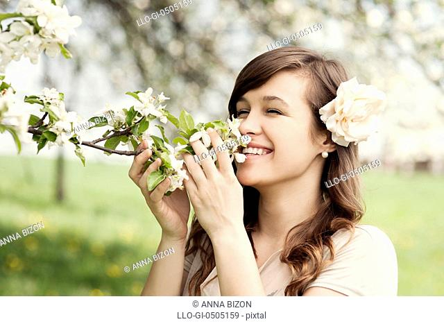 Happy young woman enjoying the fragrance of flowers. Debica, Poland