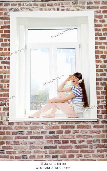 Happy woman sitting in windowsill listening to music