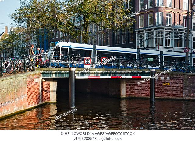 Tram crossing bridge over canal and parked bikes, Amsterdam, Netherlands, Europe