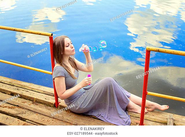 beautiful young woman with long hair wearing casual striped dress sitting on the wooden river pier, blowing soap bubbles