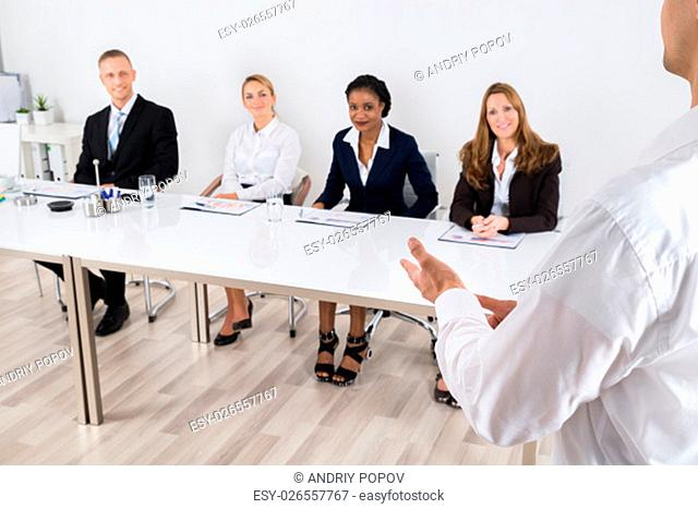 Businessperson Having Discussion With Colleague In Office