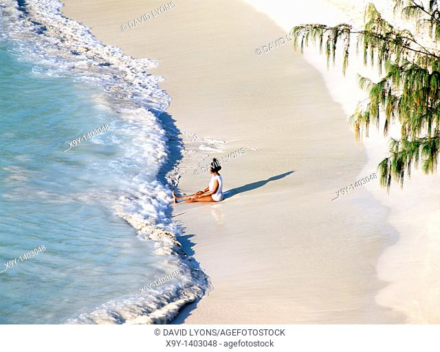 Waves break on white sand beach  Young woman relaxing at Jolly Beach, Coco Beach, west coast of Caribbean island of Antiqua