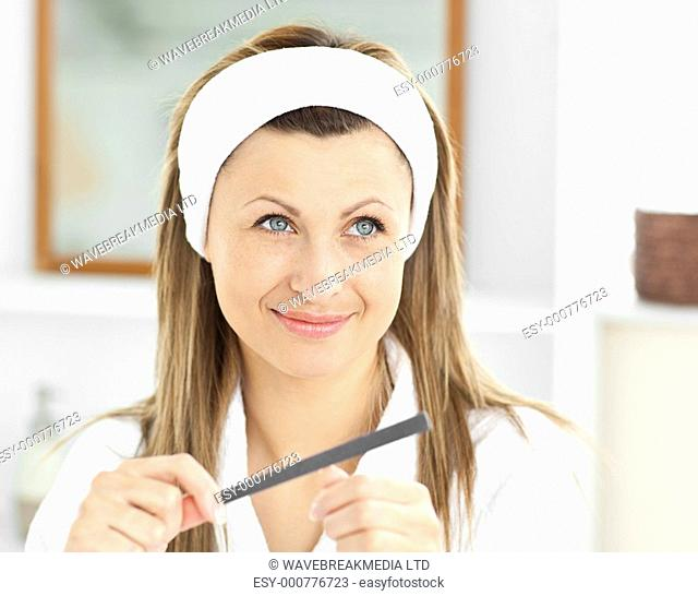 Positive woman filling her nails in the bathroom at home
