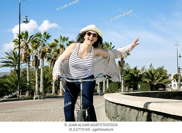 Young cheerful woman in hat and sunglasses bicycling on quay agaist palms of Gran Canaria in Spain