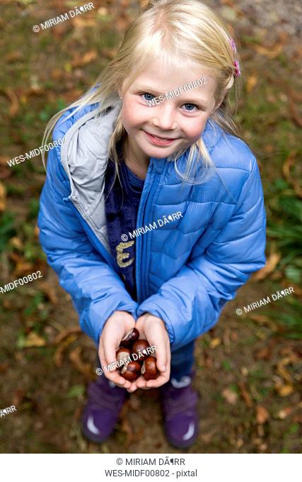 Portrait of smiling blond little girl holding chestnuts in her hands