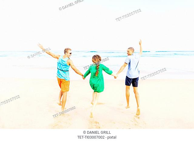 Young people holding hands and running on beach