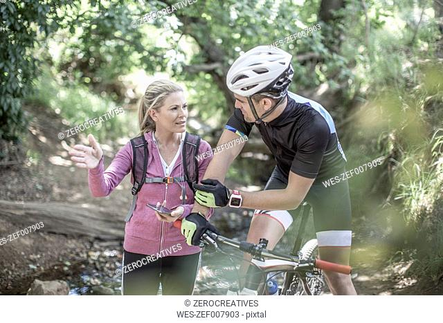 Man on mountainbike in forest talking to woman