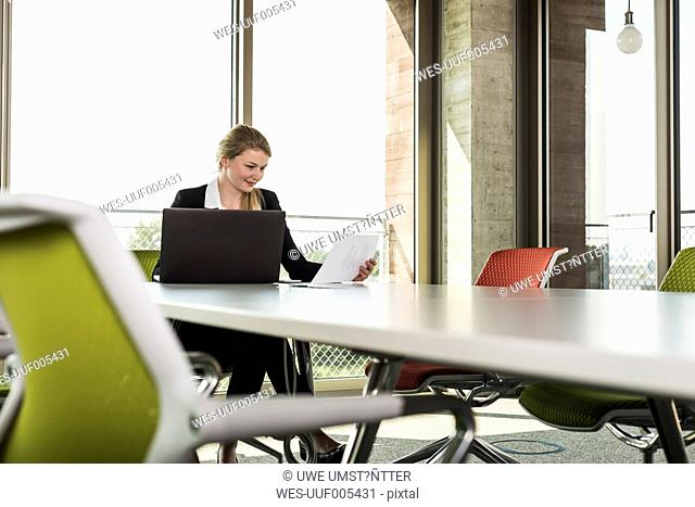 Young businesswoman in conference room looking at documents