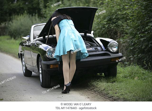 A girl looking under the bonnet of a broken down sports car