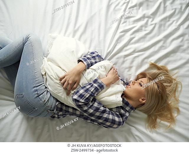 Pensive young woman lying on the bed, sad feelings
