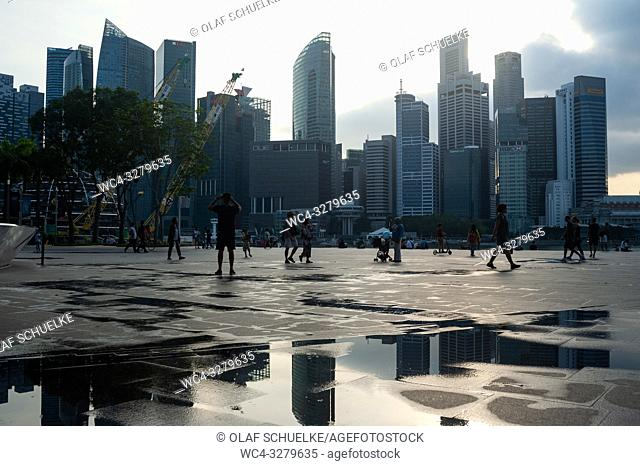 Singapore, Republic of Singapore, Asia - People at the waterfront promenade in Marina Bay with the city skyline of the central business district in the backdrop