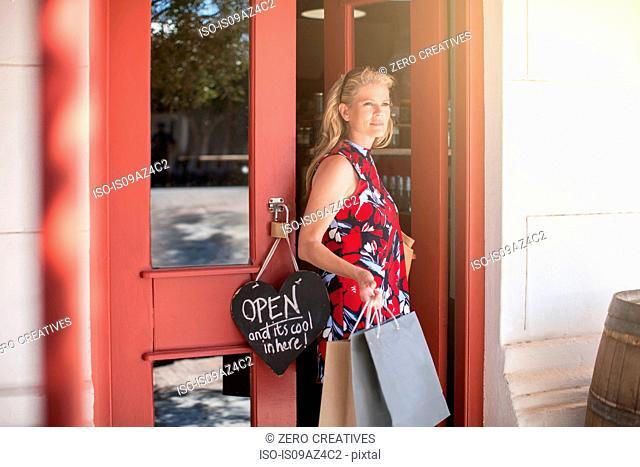 Woman leaving shop carrying shopping bags