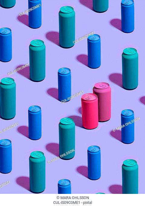 Still life of turquoise and blue drink cans in diagonal rows, with pink and purple drink cans standing out from the crowd on purple background