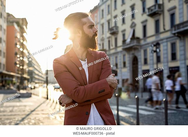 Fashionable young man waiting at backlight in the city