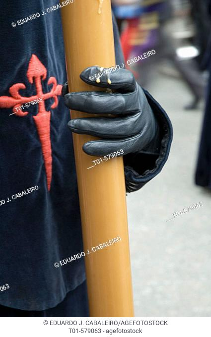 close-gloved hand and candle in the Holy Week in Seville