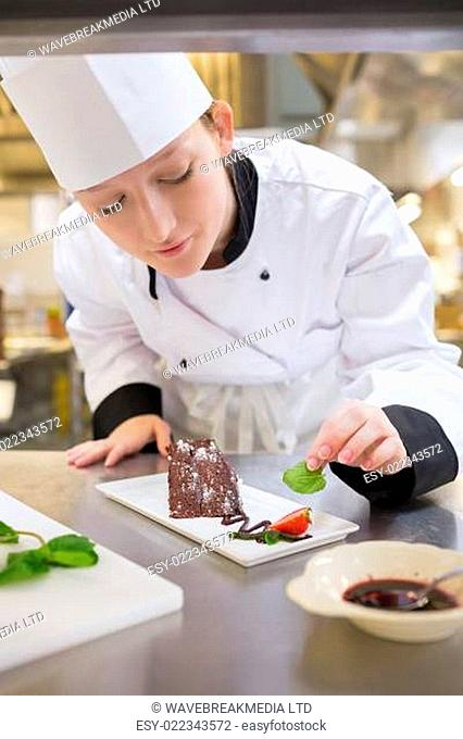 Female chef putting mint with chocolate cake in the kitchen