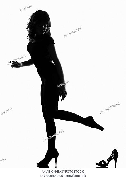 full length silhouette in shadow of a young Cinderella woman losing her shoe in studio on white background isolated