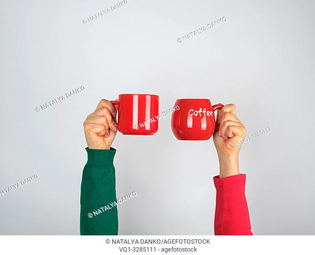 two hands in a sweater holding red ceramic mugs on a white background