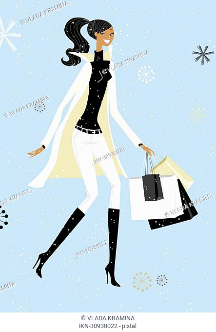 Snow falling around chic woman with shopping bags