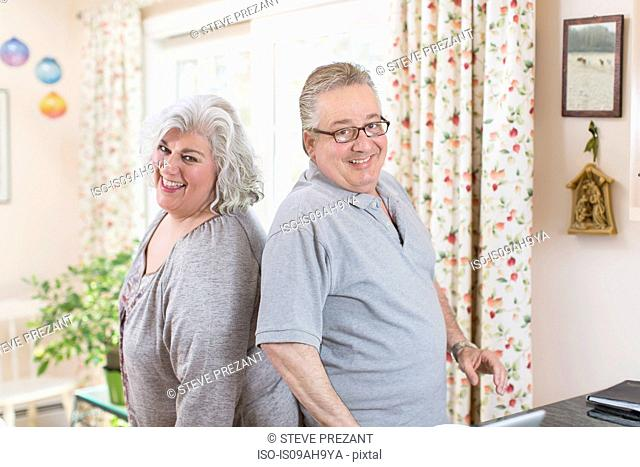 Portrait of mature couple back to back in sitting room